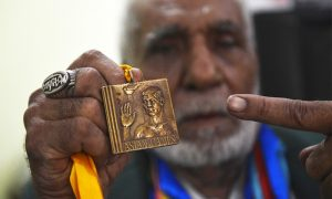 In this photo taken on June 23, 2016, former Pakistani Olympian Muhammad Ashiq holds his medals as he posses at his residence in Lahore. Ashiq, who competed for Pakistan at the 1960 and the 1964 Olympics, now scrapes by as a rickshaw driver in the teeming eastern city of Lahore. / AFP PHOTO / ARIF ALI